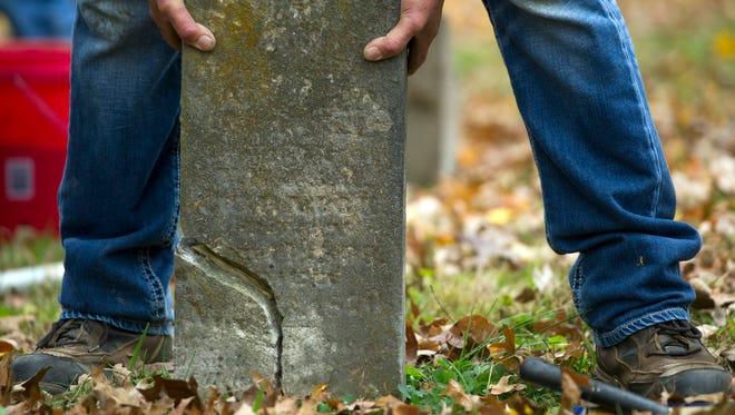 Mark Parrot repairs an old broken memorial at Old Gray Cemetery on Saturday, November 18, 2017.