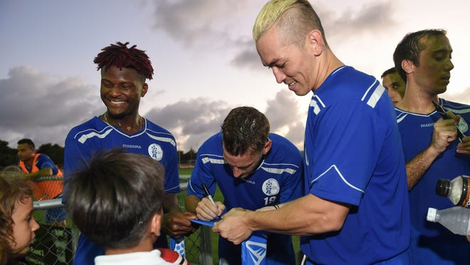 Matao players sign autographs for their young fans during a meet and greet at the Guam Football Association National Training Center in Dededo on Nov. 16.