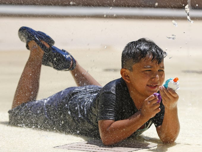 Adair Sanchez shoots water at his sibling at the splash