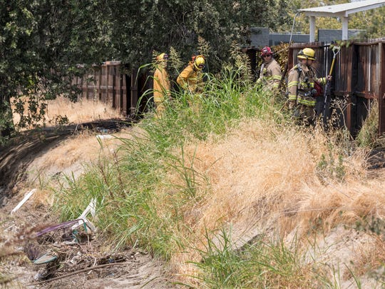 Visalia firefighters dowse a grass and fence fire near Red Lobster restaurant on South Mooney Blvd. on Wednesday, July 18, 2018. Southbound traffic was briefly narrowed to two lanes just after noon while crews worked. The fire caused an estimated $2,000 damage to about 50-feet of fence between the restaurant and Evans Ditch. Firefighters kept flames from spreading to the restaurant and no injuries were reported. Signs of recent transient activity were seen in the area and the cause is under investigation.
