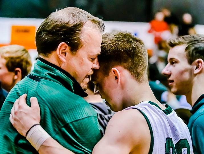 Riley Lewis ,right, of Williamson hugs his father temporary Williamston Head Coach Tom Lewis after their Class B state quarterfinal win over River Rouge Tuesday at Charlotte High School.