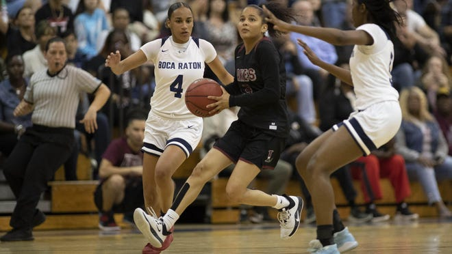 Palm Beach Lakes guard Keishmy Ayuso (5) drives between Boca Raton's Kelsi Mingo (4) and Cassidy Lowe (5) during the Rams' 63-61 win in the Class 7A-Region 3 final in Boca Raton on Friday night.
