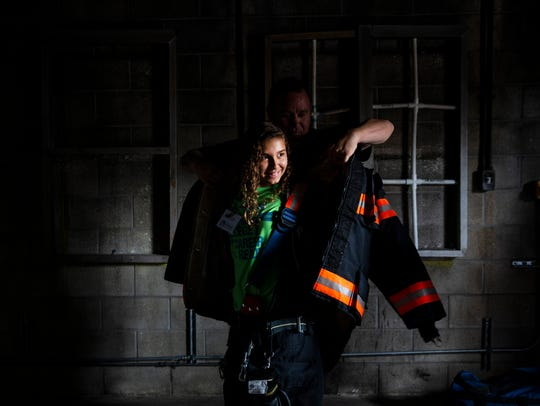 Kaitlyn Aliaga, 13, smiles as firefighter Bo Muller