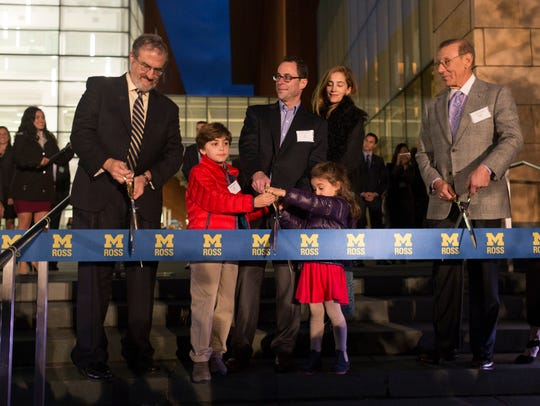 Jeff Blau, center, holds a giant pair of scissors with