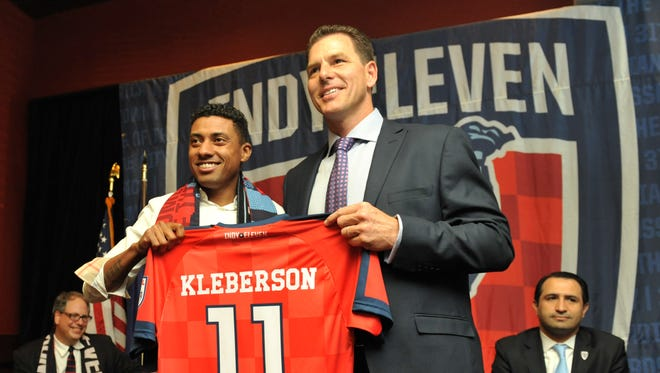 Indy Eleven coach Juergen Sommer and Brazilian midfielder Kleberson, hold up Kleberson's new jersey. It was announced that Kleberson has signed with the Indy Eleven professional soccer club, March 31, 2014.