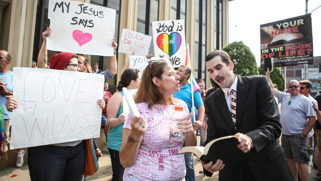 "Kennedy Missionary Baptist Church in North Carolina member Jeffrey Shook, right, attempts to read verses from the Bible to gay marriage supporters outside the Carl D. Perkins Federal Building in Ashland, Ky. before the hearing of Morehead, Ky. county clerk Kim Davis. ""My purpose here is two fold,"" Shook said. ""Take a stand for Jesus and this Bible. Two, take a stand against sin."" Sept. 3, 2015"