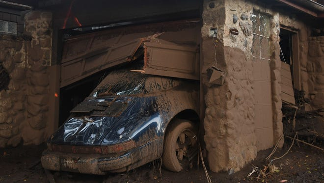 A luxury sports car is covered in mud and debris caused by a massive mudflow in Montecito, California, January 10, 2018.