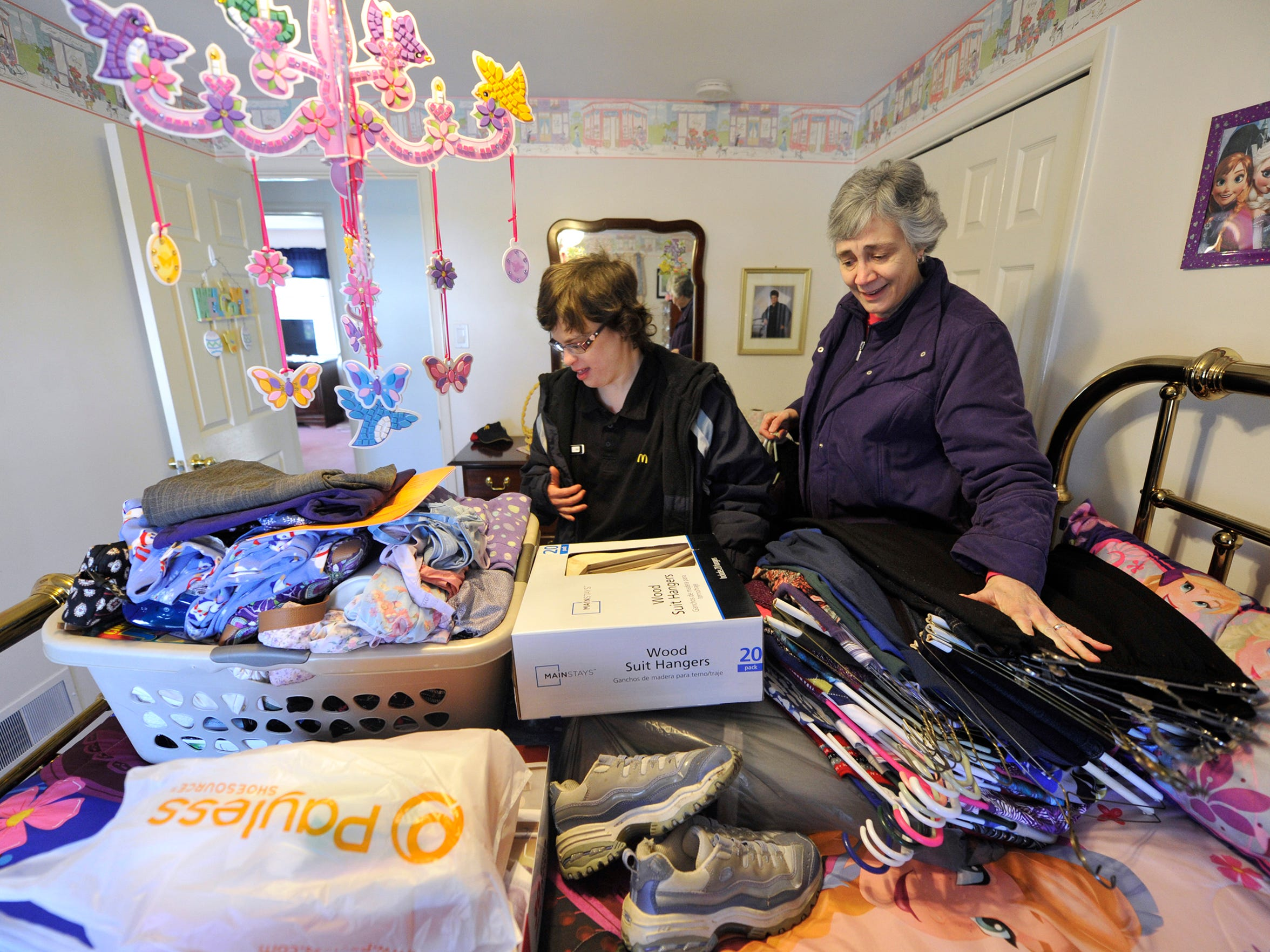 Suzanne Keim, right, helps her daughter, Sarah Keeney, unpack clothes in Keeney's bedroom of her new group home, which was opened by Jessica & Friends Community. State money helped Sarah get a spot at the home, but there isn't nearly enough money to cover everyone with special needs.