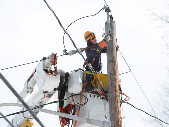 A utility worker cuts power to a primary line on Rockford
