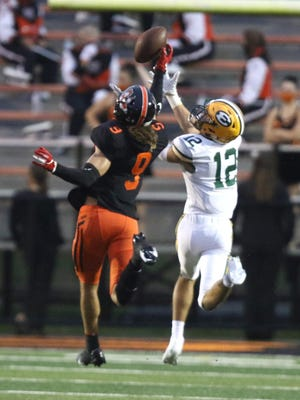 Massillon's Jayden Ballard (9) snatches an interception out of the air as he defends St. Edward's Connor Goodall on Friday August 28, 2020.