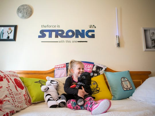 Four year-old Zoe Pedicone hugs her Darth Vader stuffed bear on her bed in her Star Wars themed bedroom on Thursday afternoon.