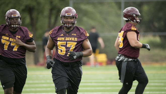 ASU offensive lineman Stephon McCray (left) and Evan Goodman (57) warm up during ASU football camp practice at Rumsey Park in Payson on Wednesday, August 3, 2016.