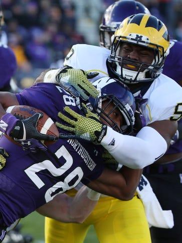 Northwestern running back Justin Jackson is tackled