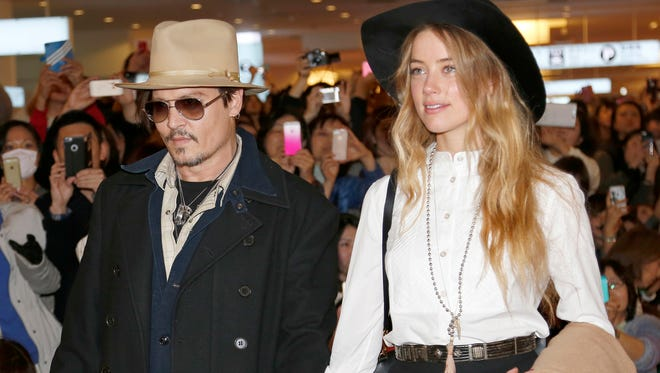 """In this Jan. 26, 2015 file photo, U.S. actor Johnny Depp and Amber Heard arrive at Haneda international airport in Tokyo to promote his latest film """"Mortdecai.""""  Heard, Depp's wife, has been charged with illegally bringing the couple's dogs to Australia."""