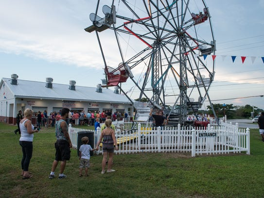 A family waits for a chance to ride the ferris wheel
