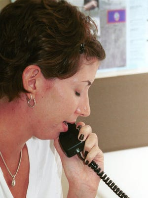 In this file photo, Crystal Googinis, a Holiday Crisis Helpline trained volunteer, answers a call.