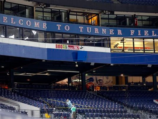 People clean a section of the lower seating area at Turner Field where a fan fell from the upper deck during a baseball game between the Atlanta Braves and the New York Yankees, Saturday, Aug. 29, 2015, in Atlanta. The fan was pronounced dead at Grady Memorial Hospital, authorities said.