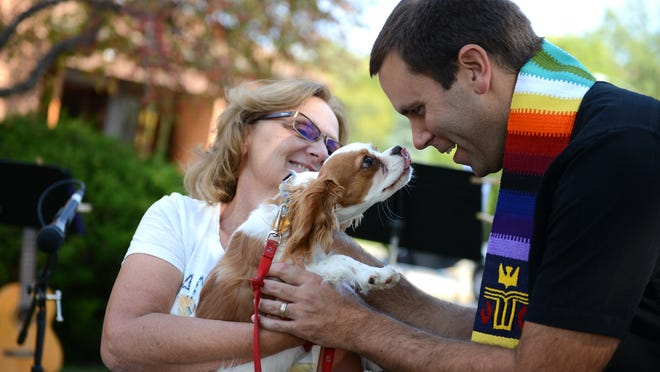 Rev. Luke Farwell greets Carol Pointer and her dog, Oscar, at the Blessing of the Animals service at First United Presbyterian Church in De Pere, Saturday, September 27, 2014.