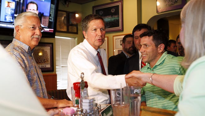 In this 2011 photo, Ohio Gov. John Kasich speaks to Price Hill Chili patrons Bill Burwinkel (left) and Nick Corey while  shaking the hand of Mary Kerley.