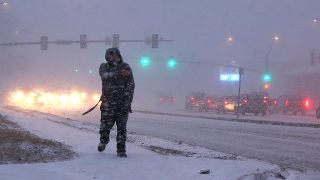 A pedestrian is caught in a quick snow storm on March 4 in Ames.