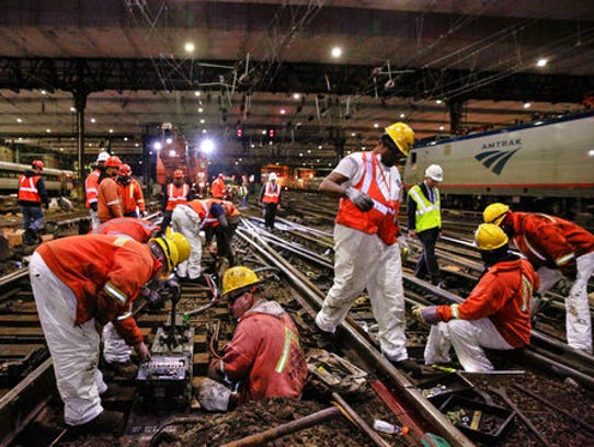 Amtrak workers do repairs on railroad tracks in a tunnel