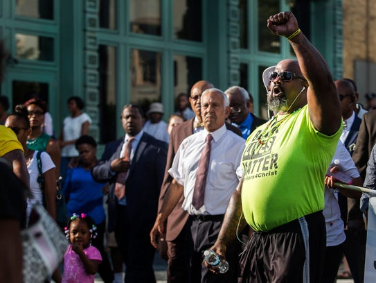 Mahkie Booker marches with his fist raised as activists