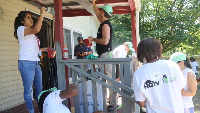 """Volunteers from Thistle Farms, HGTV and more painted the deck of a Thistle Farms home to kick off the """"She Builds"""" campaign with HGTV, Rebuilding Together and Thistle Farms on Tuesday."""