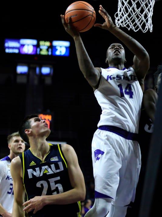 Kansas State forward Makol Mawien (14) shoots over Northern Arizona forward Brooks Debisschop (25) during the second half of an NCAA college basketball game in Manhattan, Kan., Monday, Nov. 20, 2017. (AP Photo/Orlin Wagner)