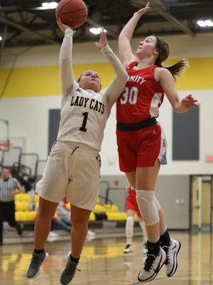 Haven's Carlee Arnold (1) shoots past Trinity Catholic's Becca Hammersmith (30) on Friday night in Haven. Haven defeated Trinity 56-29.