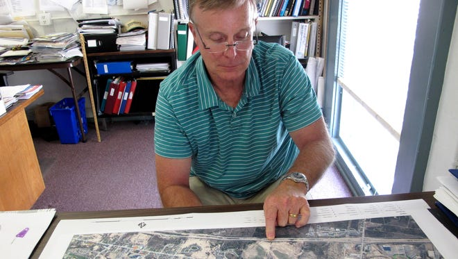 Phantom exit: Bruce Hoar, director of public works in Williston, indicates on a town map where the now-abandoned Circ Highway would have intersected with Interstate 89. Photographed in his office on Sept. 19, 2016.