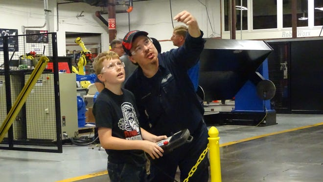 A RobotWorx employee shows Aaron French, 11, how to program one of the manufacturer's robots. French, a member of Pleasant Robotics Team, wants to work in robotics when he grows up.