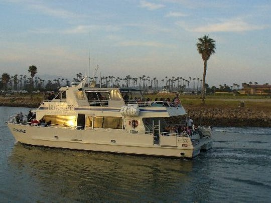 A boat cruises through the Ventura Harbor.