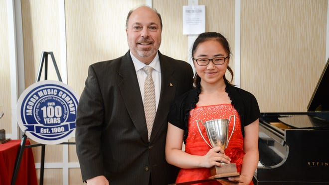 Randy Brown of Jacobs Music Company presents the Junior Artists Category Award to Elizabeth Yang.