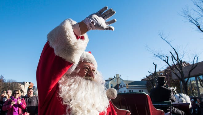 Santa waves to the crowd before entering his cabin during the Hanover Christmas Parade on Nov. 24, 2017.