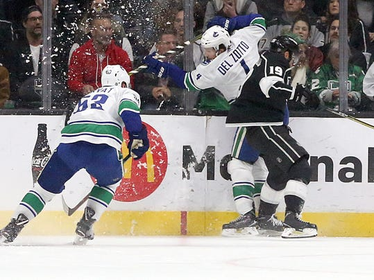 Vancouver Canucks center Bo Horvat (53) and defenseman Michael Del Zotto (4) collide with Los Angeles Kings center Alex Iafallo (19) in the first period of an NHL hockey game in Los Angeles, Monday, March 12, 2018. (AP Photo/Reed Saxon)