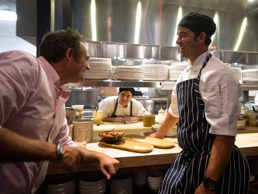 Co-Founder Hugo Matheson, left, talks to Chef Joel Ryan during a fundraiser cocktail party at Fort Collins' newest restaurant The Kitchen in old town Wednesday, June 18, 2014. Proceeds go to the nonprofit affiliate, The Kitchen Community, which is working to set up Learning Gardens in Fort Collins schools.
