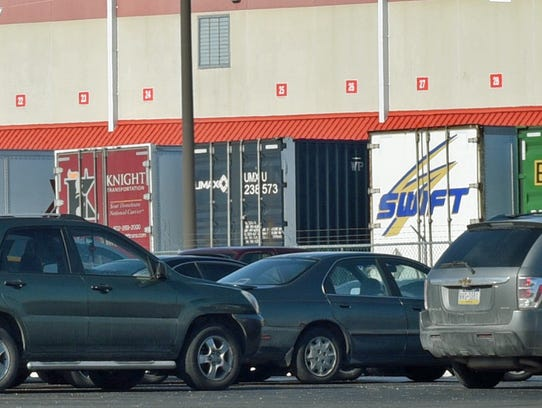 Employee cars are parked near tractor-trailers Tuesday