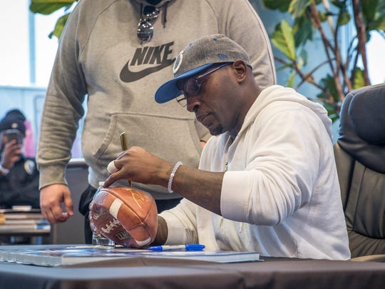 Robert Mathis, a retired Indianapolis Colts player, signs autographs for fans Tuesday afternoon at an appearance inside Toyota of Muncie. Mathis played for the Colts for 14 years before retiring at the end of this season.