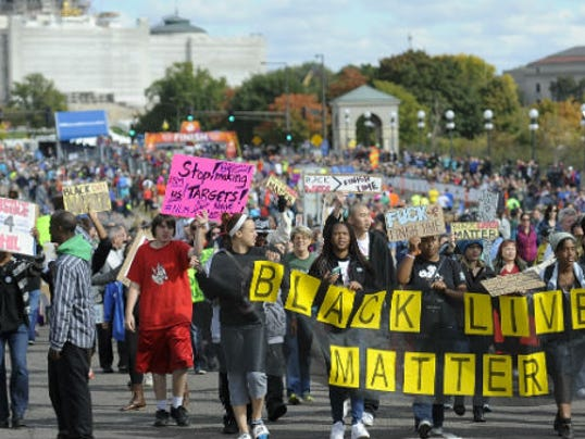 """About 100 supporters of the """"Black Lives Matter"""" march along the rout of the Medtronic Twin Cities Marathon, in St. Paul, Sunday, Oct. 4 2015. The group marched within 50 yards of barriers near the end of the course but did not disrupt the event. St. Paul police say no one was arrested."""