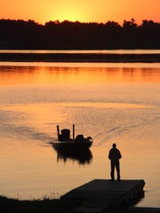 An angler waits to get picked up at a boat ramp on