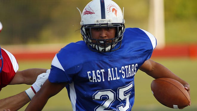 Carson Aquino runs the ball for the East during  the Ron Woyan East-West All-Star football game at Kings High School last season.