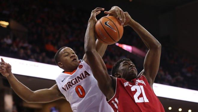 Virginia guard Devon Hall blocks the shot of Wisconsin guard Khalil Iverson in the first half at John Paul Jones Arena.