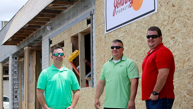 Brothers Scott, left, Kyle and Anthony Stowell stand outside their soon-to-open Johnny O's Spudnuts store on Friday in Farmington.