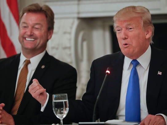 President Donald Trump gestures towards Sen. Dean Heller,