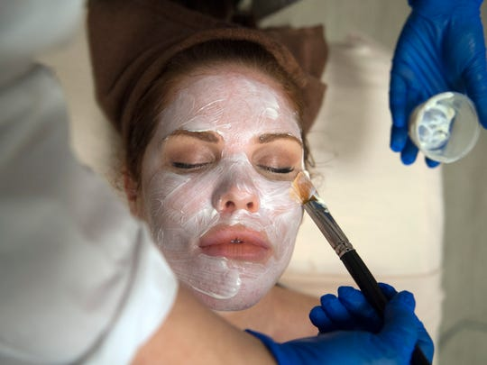 Medical esthetician Carmen Constantine applies a goji berry yogurt mask, used to calm and hydrate the skin, to Drew Davis of Marlton at Rizzieri Salon & Spa at the Moorestown Mall.