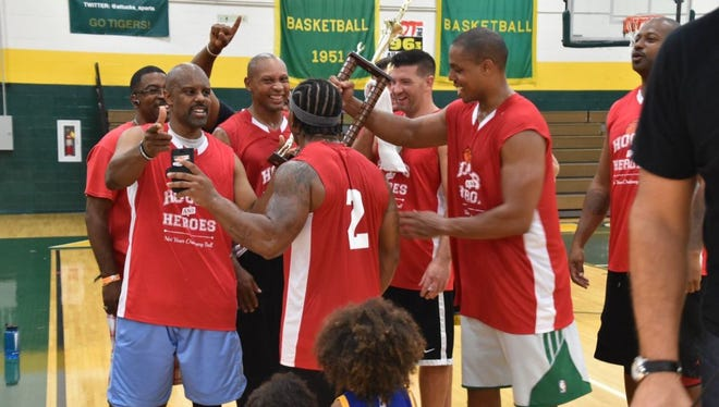 The IFD basketball team celebrates after beating the IMPD team in the fourth annual Hoops & Heroes Basketball Showdown. The event generated $82,000 for The Julian Center, a local nonprofit that fights domestic violence.
