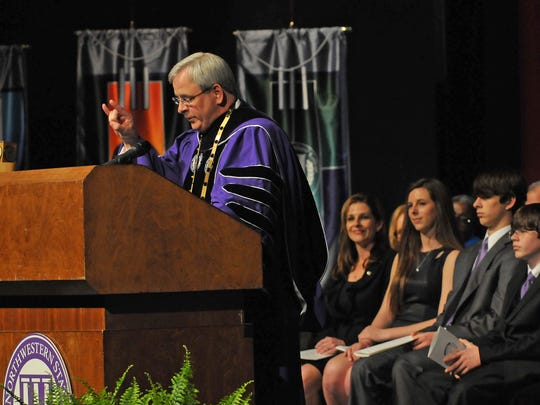 "Jim Henderson ended his investiture address with the iconic Northwestern State University ""Fork 'em."" In the background are Henderson's family, his wife Tonia and children, Reagan, Nicholas and Alexander."