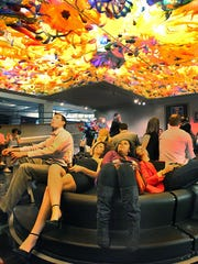 A group of adults relax on the rotating sofa below