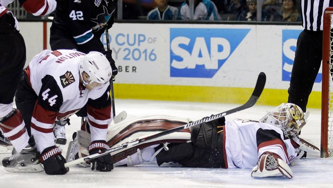 Arizona Coyotes goalie Mike Smith, right, lays down to stop a shot against the San Jose Sharks during the first period of an NHL hockey game Sunday, March 20, 2016, in San Jose, Calif.