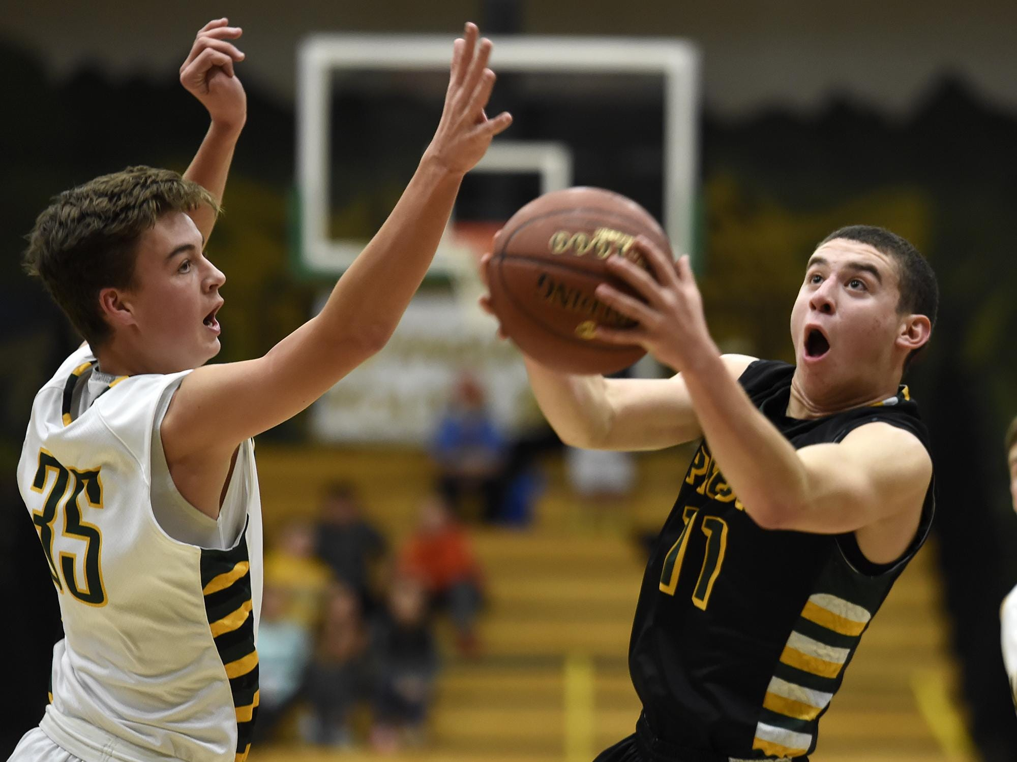 Green Bay Preble's Griffin Summers (11) takes a shot past Ashwaubenon's Anthony Guarascio (35) in the first half during Thursday night's boys basketball game at Ashwaubenon High School. The Hornets won the FRCC opener 48-31.